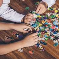 A family works together on a jigsaw puzzle
