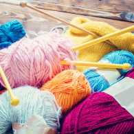 A collection of knitting needles and multi-colored skeins of yarn