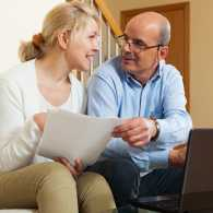 A mature couple pores over Medicare documents and the Medicare website