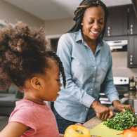 A mother and her young daughter work together to prepare a healthy meal