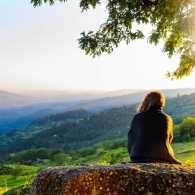 Woman watching sunset in the park; Getty Images