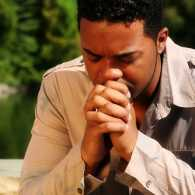 a man sits outside near trees with his elbows on his knees and his hands folded in prayer