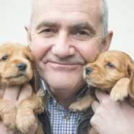 A senior citizen holding two puppies.