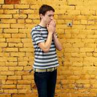 A young man bows his head in prayer