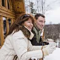 A couple looks at the snow from the balcony of their cabin with hot beverages in their hands.