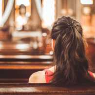 A young woman sits in a church sanctuary