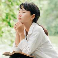 A woman prays in the outdoors