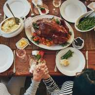 A family prays at the Thanksgiving table