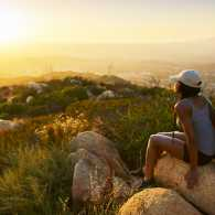 A young woman greets the sunrise from a hilltop