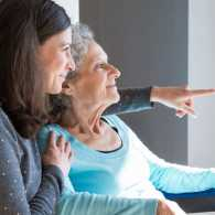Caregiver and senior woman looking out of a window