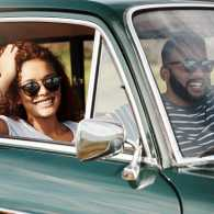 A smililng woman smiles from her car on a road trip