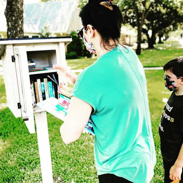 Rachel and her son adding books to a little free library; Photo credit: Rachel Koppa