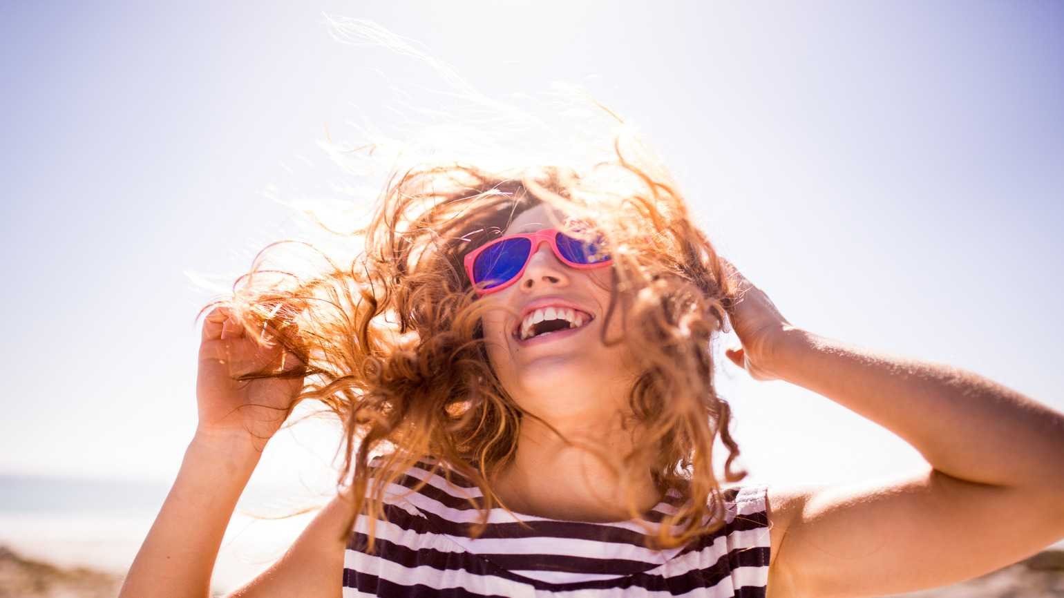 Cheerful laughing woman on the beach (Getty Images)