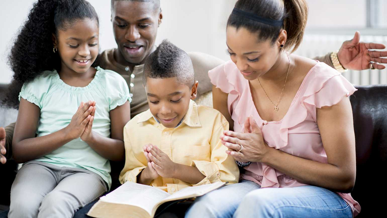 A family at home gathered in prayer.