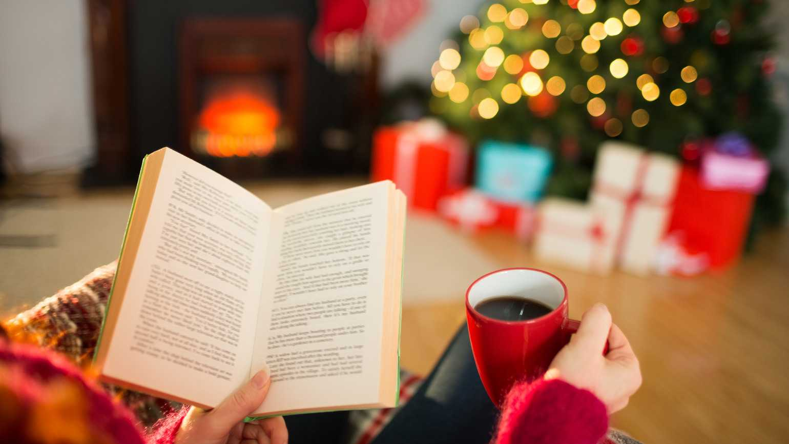 Woman reading a book and drinking coffee at Christmas (Getty)