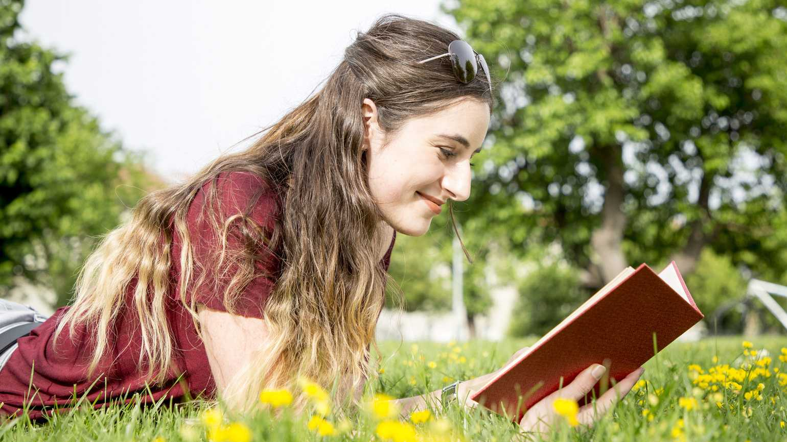 Woman reading book in field during spring (Getty Images)