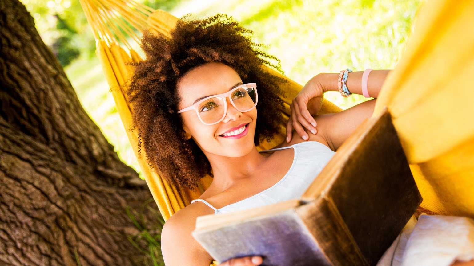 Woman reading book in yellow hammock during summer (Getty Images)