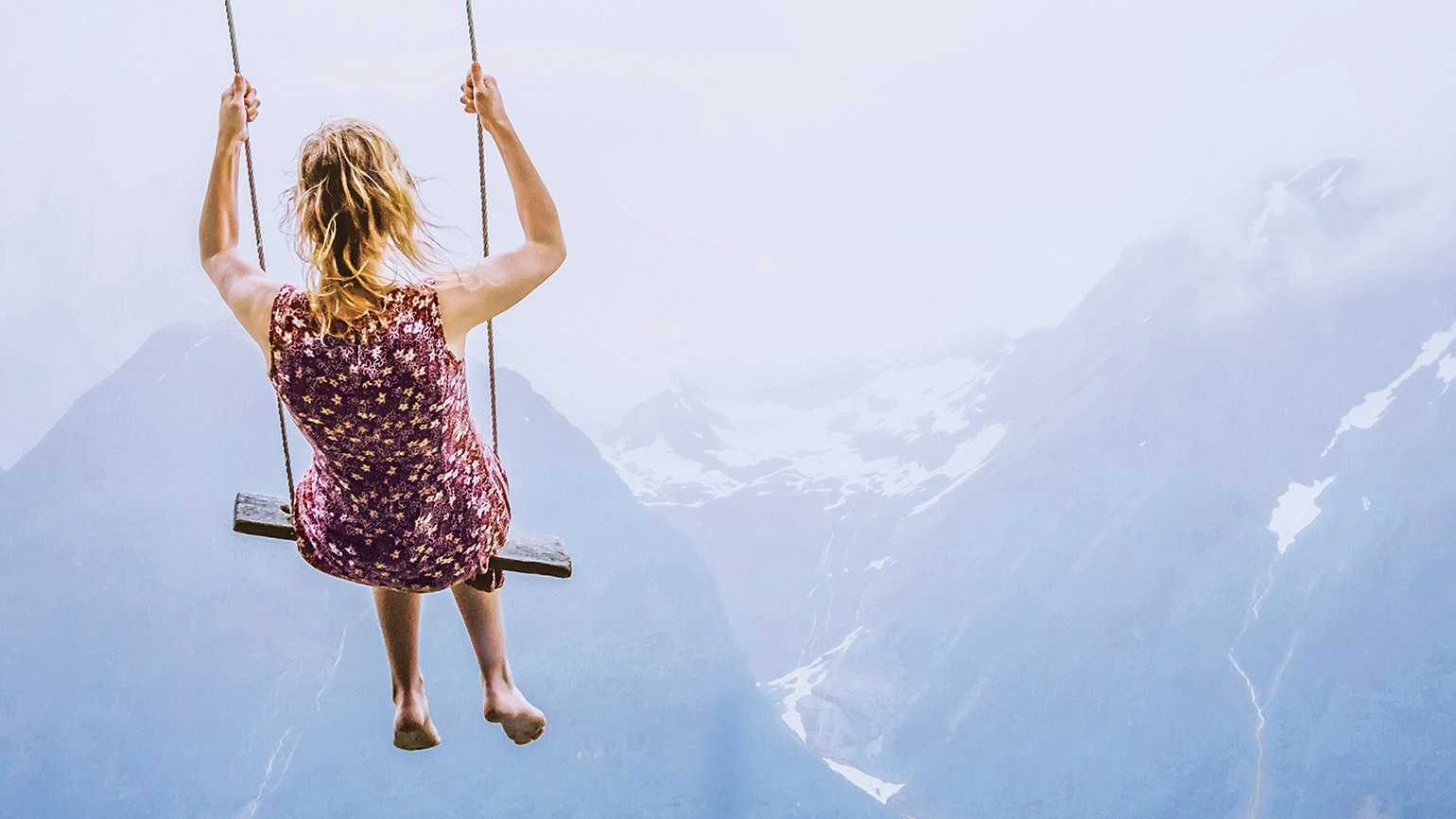 A woman on a swing in the mountains; Credit: Anna Berkut/Getty Images