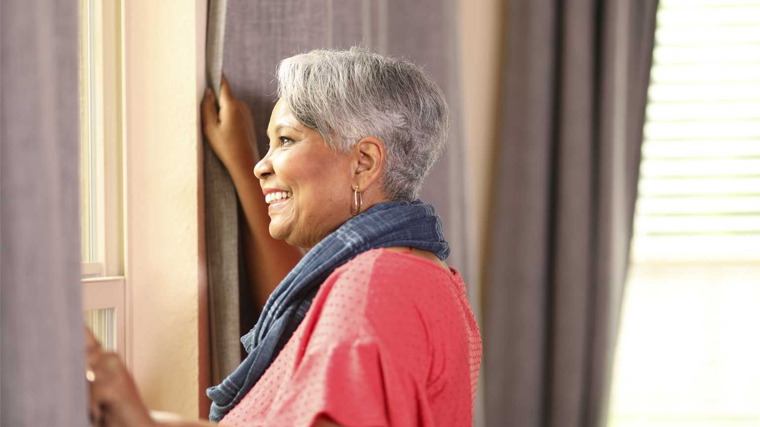 A senior woman looking out of a window; Getty Images