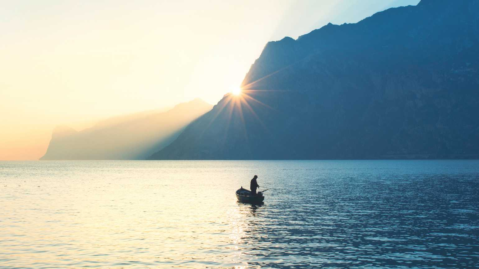 A fisherman in his boat on a lake; Getty Images