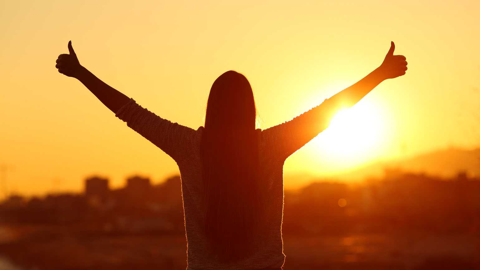 Backlight of a woman raising arms with thumbs up; Getty Images
