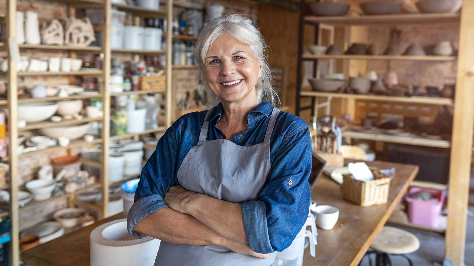 A smiling senior woman in her pottery studio