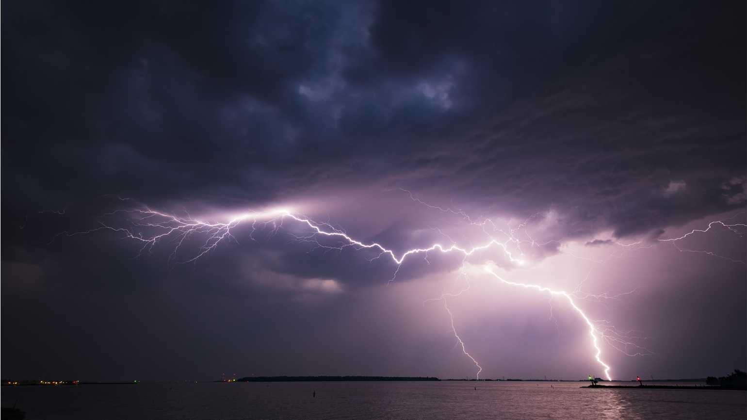 A bolt of lighning over a body of water; Getty Images