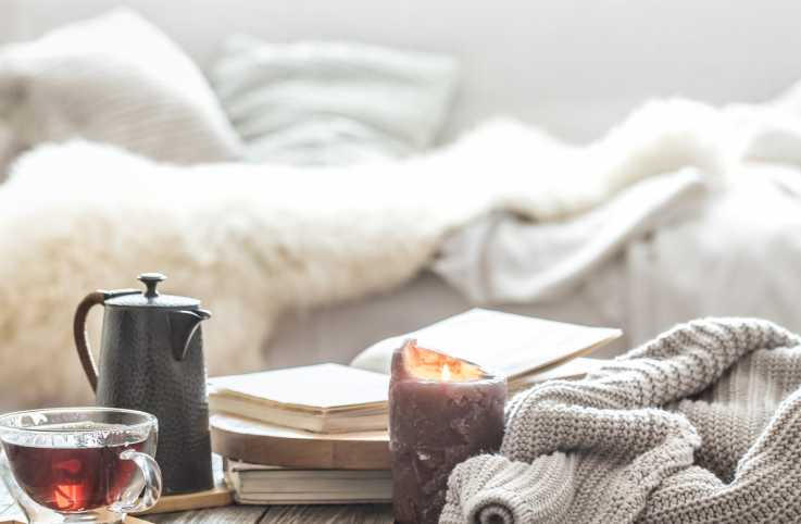Home comfort featuring blankets, tea and candles.