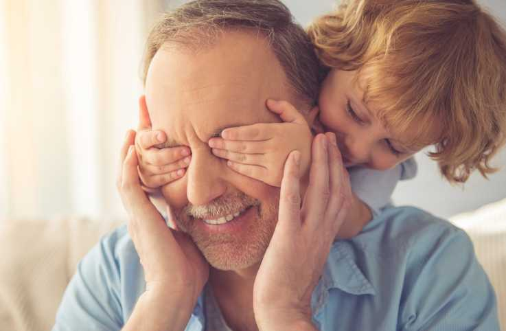 A grandfather plays peek a boo with his granddaughter.