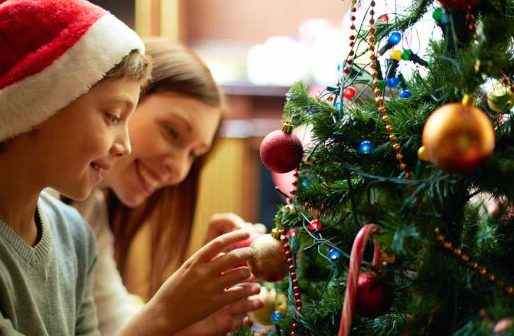 Guideposts: A mother and son smile as they decorate a Christmas tree.