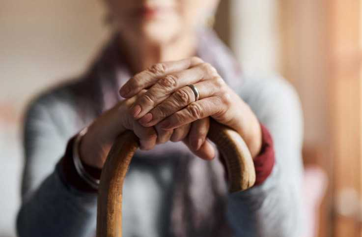 Close of a elderly woman's hands on top of a cane; Getty Images