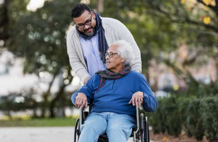 A senior man in a wheelchair conversing with his caregiver; Getty Images