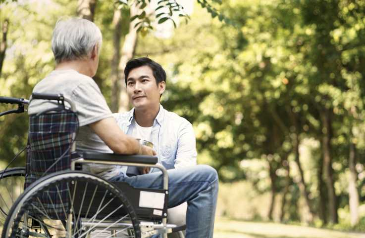 An aging mother in wheelchair converses with her caregiver son.