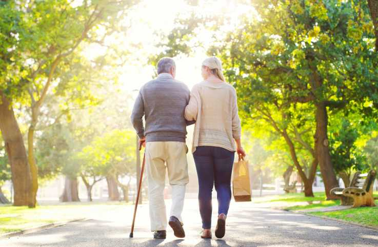 An elderly man walking with his caregiver; Getty Images
