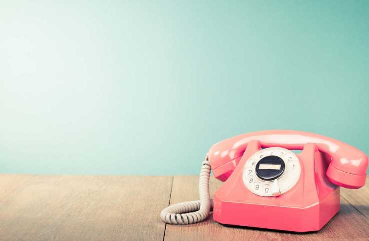 A pink vintage rotary phone; Getty Images