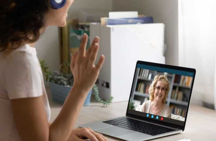 A woman talking to a loved one via video call; Getty Images
