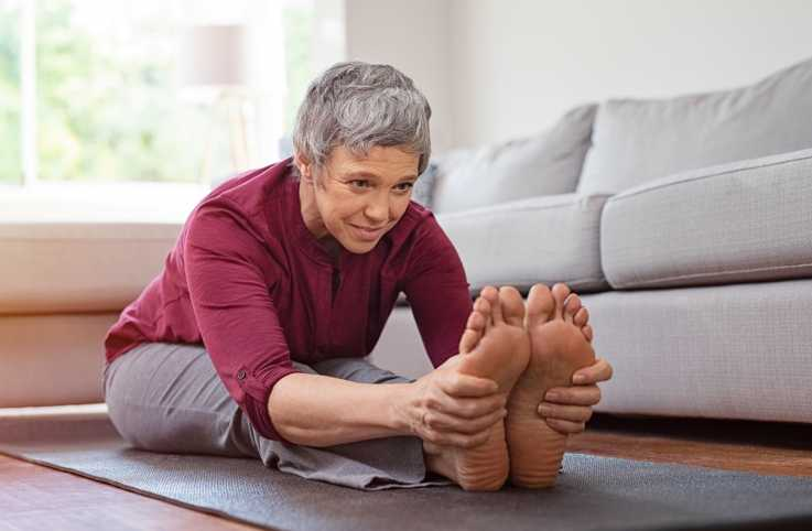 An older woman stretching in her home.