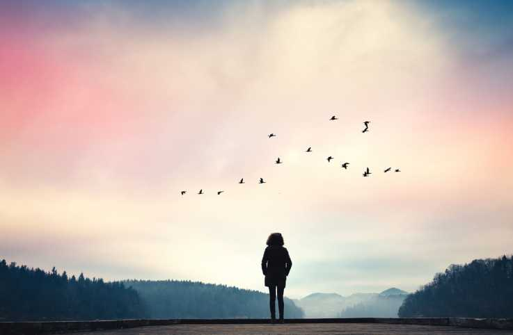 A silouette of a woman looking up at a colorful sky; Getty Images