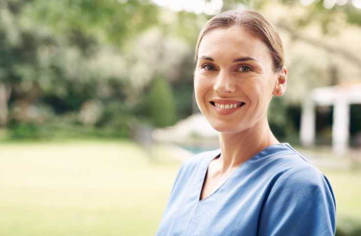 A smiling female caregiver; Getty Images