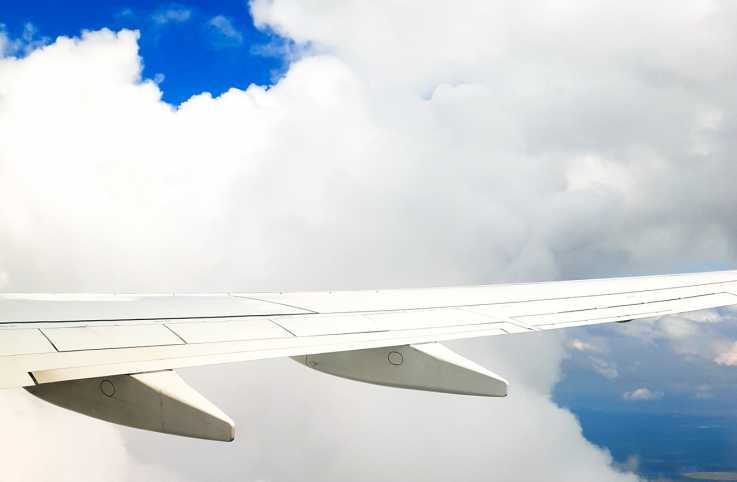 A view through an airplane window at the wing and the puffy clouds beyond
