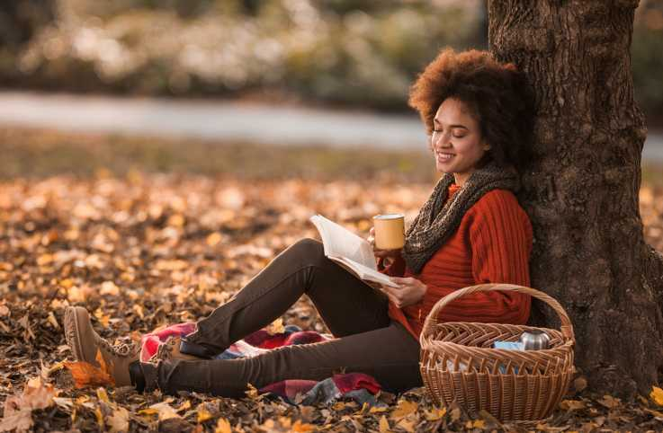 A woman reading outside with fall foliage scenery.