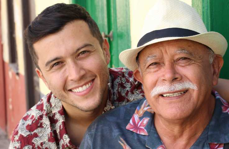 A senior man with his son smiling; Getty Images