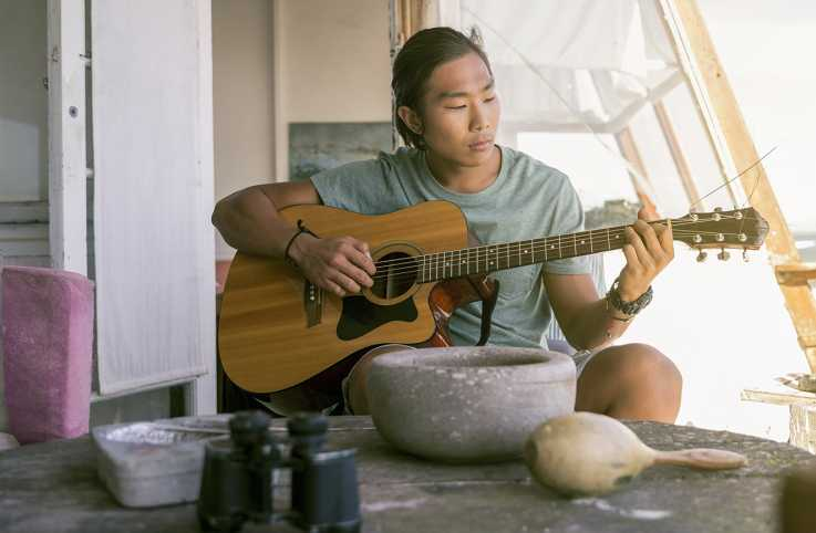A man plays his guitar on his porch for all to enjoy
