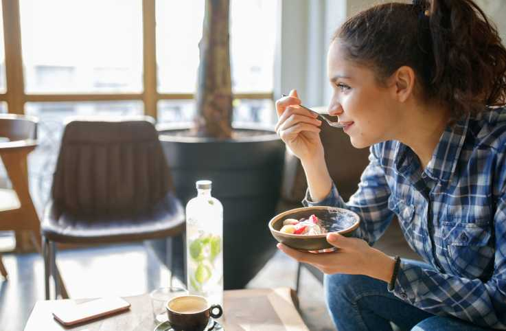 A woman eats a healthy breakfast in her home as sunlight pours in.