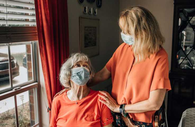 A family caregiver with patient; Getty Images