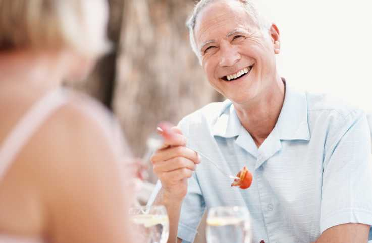 A senior man enjoying lunch outdoors; Getty Images