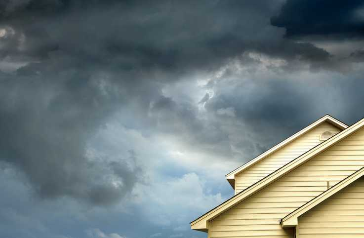 Gathering storm clouds over a house; photo credit: Getty Images