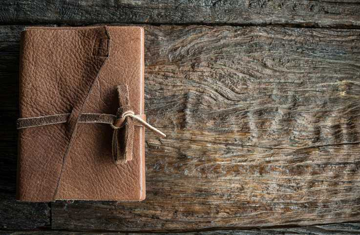 A leather-bound journal rest on a rustic wooden table; Getty Images
