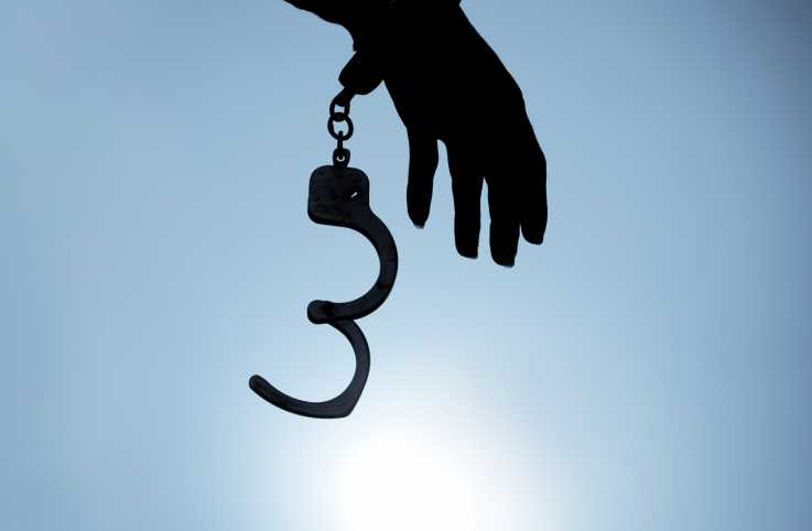 Silouette of hand with open handcuffs; Photo credit: Chanin Wardkhian/Getty Images