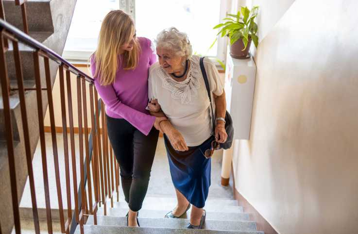A woman helping an elderly woman up the staircase; Getty Images